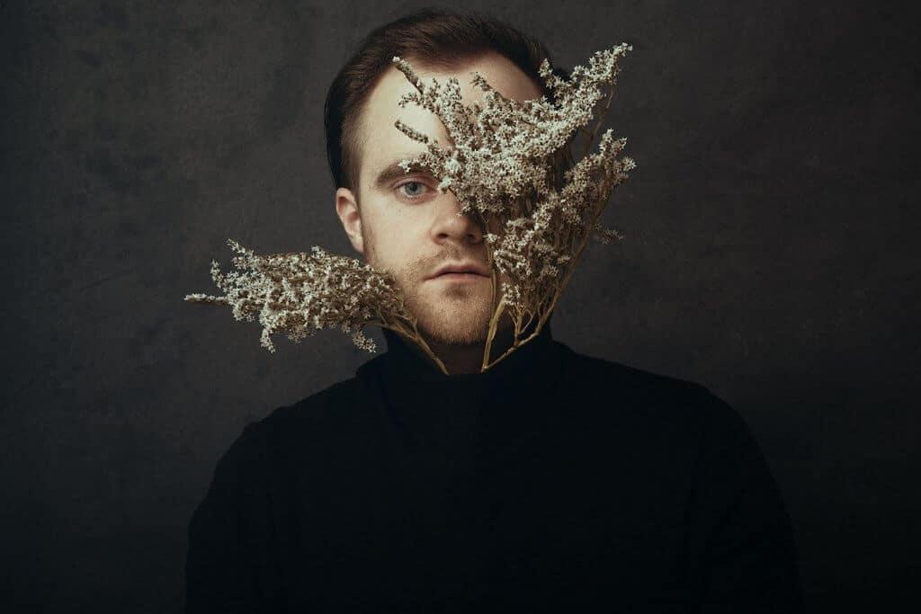Mann mit Blumen vor dem Gesicht